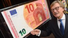 ECB board member  Yves Mersch poses with a less contentious banknote Photograph: EPA