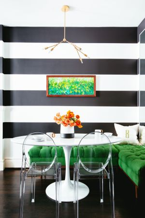 This dining room by San Francisco-based Noz Design features a strong striped wall set against emerald green seating on the L-shaped bench. This looks like velvet but is a a tufted soft tweed-like material in Key Largo Kelly Green. The dramatic black and white striped walls are painted using Benjamin Moore Black Beauty contrasted with Cloud White. This range is available at MRCB Paints. Photograph: Colin Price  Photography </br> nozdesign.co