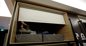 Zhang Shuangjie, an IT engineer at BaishanCloud, drops the curtain as he prepares to sleep around midnight in an individual sleeping quarter in the office. Photograph: Jason Lee/Reuters