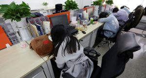 Employees at Goopal Group take a nap in their seats after lunch, in Beijing. Photograph: Jason Lee/REuters