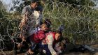 Syrian migrants cross under a fence as they enter Hungary at the border with Serbia last August. Photograph: Reuters