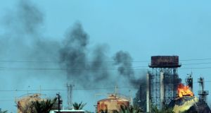 Flames and smoke rise from tanks after a suicide bomb attack on the Taji gas plant, about 20 kilometres north of the Iraqi capital Baghdad. Photograph: Sabah Arar/AFP/Getty Images