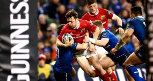 Darren Sweetnam in the red of Munster is tackled by two Leinster players at the Aviva Stadium earlier this season. Photograph: James Crombie/Inpho