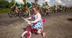 Three-year-old Anna Crombie rides her bike as the  Ras passes through Rahugh on its way to Charleville. Photo: Morgan Treacy/Inpho
