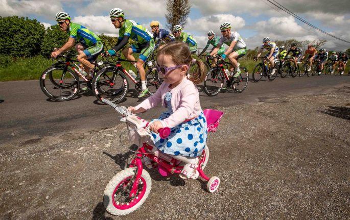 Three-year-old Anna Crombie rides her bike as the Ras passes through Rahugh e695b353c