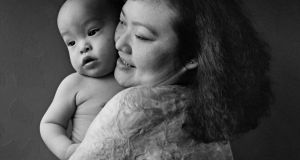 Kim Phuc pictured with her son Thomas, now aged 22, in 1995. 'When I was growing up, the pain was so sharp, it was like I'd been cut by a knife. As I get older, the pain is different, it is deep in there and stays there.'