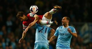 Mathieu Flamini (in air) during a  Premier League soccer match between Arsenal and  Manchester City. Photograph: REUTERS/Eddie Keogh