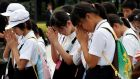 Students pray in front of the cenotaph for the victims of the 1945 atomic bombing, at Peace Memorial Park in Hiroshima. Photograph: Toru Hanai/Reuters