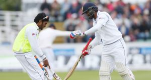 Sri Lanka's Dimuth Karunaratne (R) exchanges his bat on the third day of the second test cricket match between England and Sri Lanka at the Riverside in Chester Le Street, north east England on Sunday. Photograph: Scott Heppel/AFP