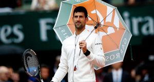 World number one  Novak Djokovic uses an umbrella as he checks out the conditions at Roland Garros in Paris. Photograph: Yoan Valat/EPA