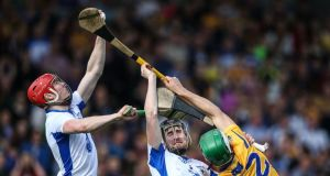Waterford's Tadgh De Burca catches a high ball over teammate Barry Coughlan and Aaron Shanagher of Clare during the league final replay. Photograph: Cathal Noonan/Inpho