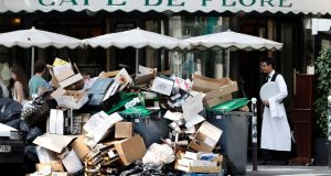 A waiter stands near a pile of rubbish bags in front of the Cafe de Flore in Paris on Wednesday, as a strike by garbage collectors continued. Photograph: Charles Platiau/Reuters