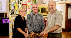 Savina Donohoe, curator of Cavan County Museum, turf cutter Jack Conway, and Andy Halpin, assistant keeper, Irish Antiquities Division, National Museum of Ireland, with a prehistoric 10kg lump of bog butter thought to have been a gift to the gods, which was found by turf cutters. Photograph: Cavan County Museum/PA Wire