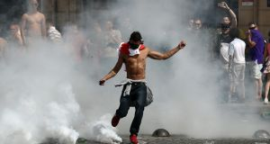 An England fan kicks a tear gas canister as fans clash with police. Photo: Carl Court/Getty Images