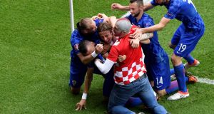 Luka Modric is mobbed after scoring the winner for Croatia against Turkey in Paris. Photograph: Afp
