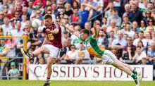 Westmeath's John Heslin  kicks a point despite  the attempted challenge of Offaly's Seán Pender during the Leinster SFC quarter-final at  Cusack Park in Mullingar. Photograph: Tom Beary/Inpho