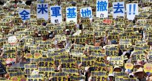 Protesters raise placards  during a rally against the US military presence on the island of Okinawa, Japan. Photograph:  Kyodo/via Reuters