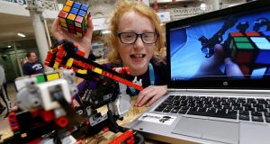 11-year-old  Katie Reilly,  from Kimmage, Dublin,  with her Lego Mindstorms robot that solves  Rubik's Cubes at CoderDojo's Coolest Projects Awards  at the RDS, Dublin. Photograph:  Conor McCabe/MediaConsult