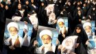 Anti-government protesters hold posters of Shia cleric Ayatollah Sheikh Isa Qassim during an anti-government protest organised by  Al Wefaq in   2013. Photograph: Hamad I Mohammed/Reuters