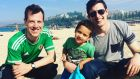 Jonathan Drennan (left) with Ben and Caleb (2) Hewett on Coogee Beach in Sydney: 'I am not alone in my need to watch the games live, somehow believing that my remote presence via a shaky wifi Australian connection will be the lucky charm that helps Ireland's football teams north or south of the border to win.'