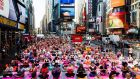 People participate in a group yoga class in Times Square as part of the 14th annual 'Solstice in Times Square: Mind Over Madness Yoga' to mark the summer solstice in New York. Photograph: Justin Lane/EPA