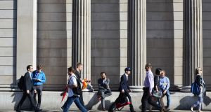 Commuters pass outside the Bank of England in London on Friday morning Photograph: AFP