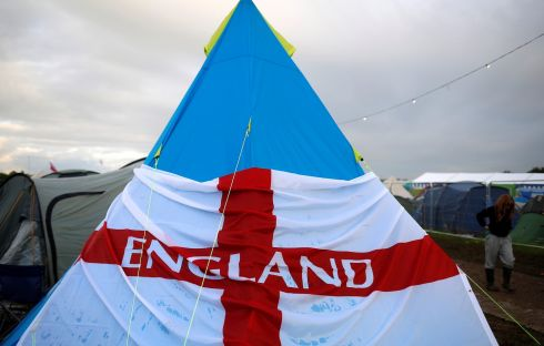 A reveller walks past a tent wrapped with the English flag during the Glastonbury Festival at Worthy Farm in Somerset, Britain, June 24, 2016.  Photograph: Stoyan Nenov / Reuters