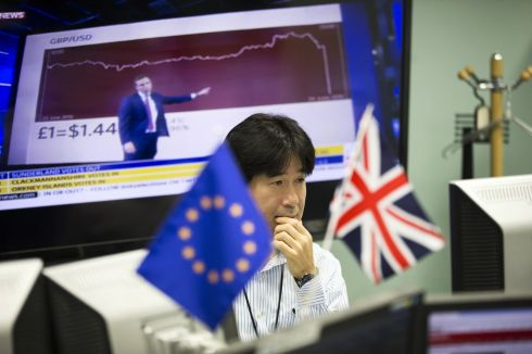 "An employee works in front of computer monitors near a European Union (EU) flag, left, and a Union Jack, at a foreign exchange brokerage in Tokyo, Japan, on Friday, June 24, 2016. The pound tumbled with the euro and U.K. equity index futures after early results from Britain's referendum on membership of the European Union put the ""Leave"" campaign ahead, suggesting the risk of a so-called Brexit is greater than opinion polls implied.  Photograph:Tomohiro Ohsumi/Bloomberg"