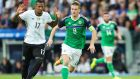 Northern Ireland's Steven Davis tracks Germany's Jerome Boateng. Photograph: Presseye