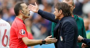 Italy   coach Antonio Conte speaks to referee Cuneyt Cakir.  Photo: Darren Staples/Reuters