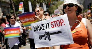 A woman holds a sign advocating for gun control while marching with the Moms Demand Action against gun violence contingent at the San Francisco LGBT Pride parade in San Francisco, California, on Sunday. Photograph: Elijah Nouvelage/Reuters