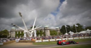 Red Bull Racing roar past the main house on its way up the hill at the Goodwood Festival of Speed