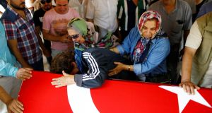AIRPORT ATTACK: Relatives of Gulsen Bahadir, a victim of Tuesday's attack on Ataturk airport, mourn at her flag-draped coffin during her funeral ceremony in Istanbul, Turkey,  June 29th, 2016. Photograph: Osman Orsal/Reuters