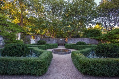 The gardens of this 1920s' estate, built on Chicago's north shore, are stunningly formal, in a French style, with multiple annual and perennial plantings. Mariani Landscape Design added a dramatic rose arbor that runs along the length of the grand lawn, connecting it to the fountain garden. The garden rooms are connected by pathways, each an intimate space, but connected by careful use of boxwood hedges. Marianilandscape.com. Photograph: Linda Oyama Bryan