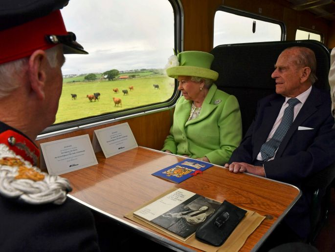 TUESDAY: Britain's Queen Elizabeth and Prince Philip travel by steam train from Coleraine Railway Station to Bellarena Railway Station, in Northern Ireland. Photograph: Arthur Edwards/Reuters