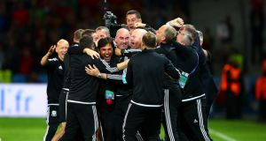Chris Coleman and the  Wales backroom staff  celebrate the victory over Belgium in Lille. Photograph:   Clive Rose/Getty Images