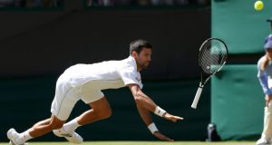 No 1 seed Novak Djokovic slips and drops his racket during his match against America's  Sam Querrey at Wimbledon. Photograph: Paul Childs/Reuters