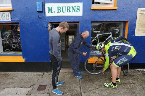 A drop of Oil from Mikey Joe Burns, Sneem and his son Aodhan,  puts Ian Stryker From Abbeyfeale, back on his bike, in the 33rd Annual Ring of Kerry Charity Cycle.   Photograph: Valerie O'Sullivan