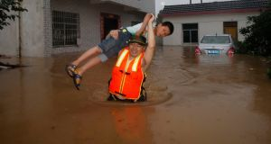 In this photo taken on  July 2nd, 2016, a rescue worker lifts a child through flood waters as residents are evacuated after the Jushui river broke the dyke and flooded Tuhe village in Wuhan in central China's Hubei province. Photograph: AP