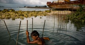 A boy plays on rebar being used to build a new sea wall to replace one that failed during last year's king tide in Betio, a town on the island of South Tarawa in Kiribati, whose fate in the face of climate change is so precarious that the government is effectively planning its own demise. Photograph: Josh Haner/New York Times