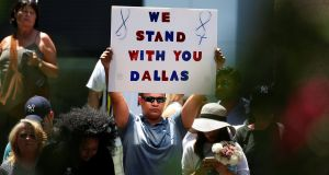 A man holds a sign of support during a prayer vigil in a park following the  shooting dead of five police officers in Dallas, Texas, US, July 8th, 2016. Photograph: Carlo Allegri/Reuters