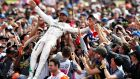 Lewis Hamilton falls back into his supporters after claiming a third consecutive British Grand Prix win at Silverstone. Photograph:   Mark Thompson/Getty Images