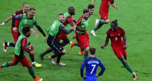 Portugal celebrate Eder's winner as Antoine Griezmann looks on at the Stade de France. Photograph: Epa