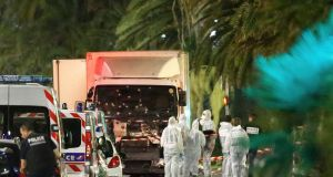 French police forces and forensic officers stand next to a truck that ran into a crowd celebrating the Bastille Day national holiday on the Promenade des Anglais killing at least 84 people in Nice, France, on Friday. Photograph: Eric Gaillard/Reuters