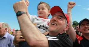 Tyrone's Mickey Harte celebrates with his grandson Michael after the Ulster final victory over Donegal. Photograph: Lorraine O'Sullivan/Inpho