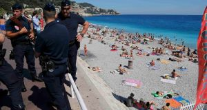 French CRS police patrol on the walkway above a public beach after the Bastille Day truck attack. Photograph: Pascal Rossignol/Reuters