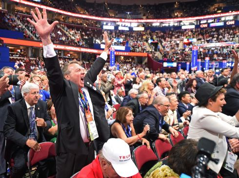 A delegate cheers during the roll call of states on the second day of the Republican National Convention on July 19, 2016 at Quicken Loans Arena in Cleveland, Ohio.  AFP PHOTO / Robyn BECKROBYN BECK/AFP/Getty Images