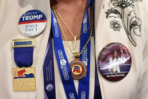 A delegate sports pro-Trump pins as she attends the roll call of states on the second day of the Republican National Convention .  AFP PHOTO / Robyn BECKROBYN BECK/AFP/Getty Images