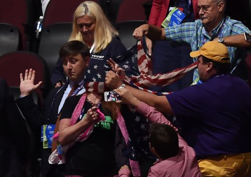 A Code Pink protestor's face is covered with the American flag as she is restrained during the Republican National Convention on July 19, 2016 at Quicken Loans Arena in Cleveland, Ohio.  AFP PHOTO / Timothy A. CLARY