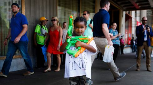 Jayla Light holds plastic guns while her father, Stevedore Crawford Jr., of Delaware, Ohio, speaks nearby about the Tamir Rice shooting, on a street near the Republican National Convention in Cleveland, Ohio, USA, 19 July 2016.  EPA/JUSTIN LANE